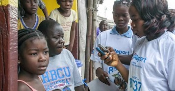 adolescent girls, holding brochures, read text messages on mobile telephones in the West Point neighbourhood of Monrovia, the capital. The girls, who are 'U-Reporters' are helping to raise awareness in the community about Ebola virus disease