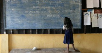 A student reads from the blackboard during class in Cambodia.