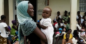 Anirwoth Winnie, 17, holds her 7-month-old daughter, Delight, outside the UNICEF-supported Health Center III in Nyaravur, Nebbi district, West Nile, Uganda.