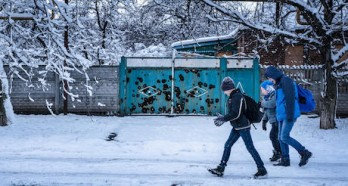 Twelve-year-old Sasha, far left, walks to school in the town of Avdiivka, Donetsk Oblast, Ukraine, November 2017. Heavy shelling and a lack of heat have reduced his school's hours to three days a week, with 20-minute class sessions.