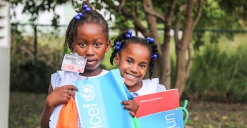 Two girls from Barbuda hold school supplies and other items they received from UNICEF after Hurricane Irma devastated their island home, forcing them to flee with many other children and families to Antigua.