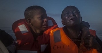 An 11-year-old girl from Nigeria (left) comforts her younger brother aboard a rescue boat after they were picked up from an overcrowded dinghy in the Mediterranean Sea, en route to Italy, about 14 miles north of Sabratha, Libya, on July 28, 2016.