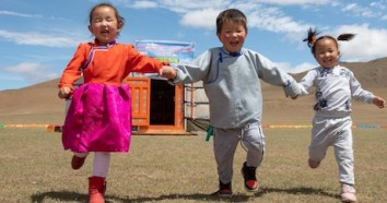 "On June 17, 2018, three laughing children play outside their newly opened mobile ""ger"" kindergarten in the Janjin bagh area of Mongolia's Bayankjongor Province. The mobile kindergarten provides early education for more than 20 children in the nomadic herd"