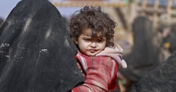 Syrian families displaced by war cross a desert in harsh conditions to a UNICEF-supported shelter.