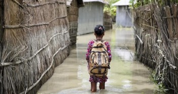 A child wades through flood water on her way to school in the Kurigram district of northern Bangladesh during monsoon season in August 2016.