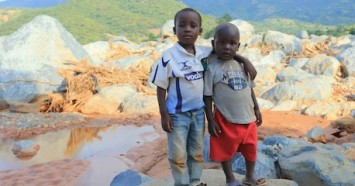 Brothers Anesu Mupfute (left) and Future Gore stand near the spot where their house was swept away when Cyclone Idai hit Coppa in Risitu Valley Chimanimani, Zimbabwe in March 2019.