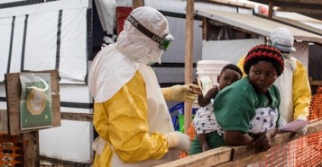 A health worker wearing a gown, gloves, mask and goggles checks a child potentially infected with Ebola being carried on the back of a caregiver at the Ebola Treatment Center of Beni, North Kivu province, Democratic Republic of Congo on March 24, 2019.