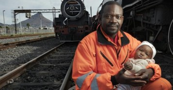 In May 2019, Congolese refugee Dieu-Merci Matala, 44, holds his infant daughter, Grace, near the Transnet harbor facility where he works in Cape Town, South Africa.