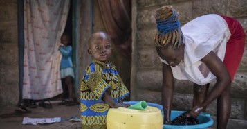 Cinderella Akinyi Othiambo, 22, washes clothes as her one-and-a-half-year-old nephew, Duncan Makoa, looks to the camera, outside her home in Mathare, an informal settlement in Nairobi, Kenya.