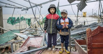 Brothers Phuc Thinh, 7, (left) and Thanh Phuc Khang, 5, stand in the ruins of their home after a series of destructive typhoons and floods in Le Thuy, Quang Binh, Vietnam.