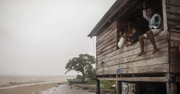 On Novermber 2, 2020, children sit on a beach house window as Hurricane Eta approaches in Bilwi, Puerto Cabezas, Nicaragua. Hurricane Iota is expected to make landfall nearby on November 16.