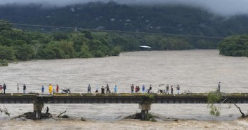 People watch the Humuya river flooding due to heavy rains caused by Hurricane Eta, in Santa Rita, northern Tegucigalpa, Honduras on November 3, 2020.