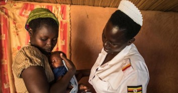 A UNICEF-trained nurse midwife helps 28-year-old Lucy Atikoru wrap her newborn close to her body at the Omugo Health Center in Uganda on December 19, 2019.