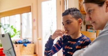 On March 20, 2020 in Connecticut, USA, 8-year-old Luka has a snack while working on a distance learning assignment while his school is closed to contain the coronavirus outbreak.