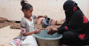 On April 4, 2020, Fatima pours water to help her mother wash her hands thoroughly, in a center for internally displaced persons in Aden, Yemen.