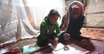 On April 9, 2020, 9-year-old Maria follows a pre-recorded lesson on her father's mobile phone in a tent at the Kili IDP camp in rural Idlib, Syria.