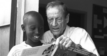 "Former UNICEF USA Executive Director James P. ""Jim"" Grant shares a book with a boy at a community center near Abidjan, Côte d'Ivoire."