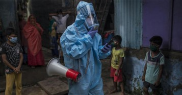 A UNICEF coordinator for COVID-19 awareness program walks through an impoverished neighborhood in Mumbai, India, where UNICEF and partners are improving sanitation and other living conditions to help contain the spread of the virus.