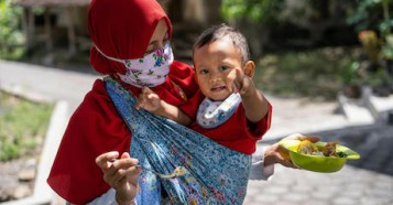 A mother feeds her year-old son at home in Paseban village, Central Java province, Indonesia, where UNICEF supports nutrition programs.