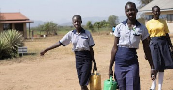 17-year-olds Margaret and Elizabeth (left and center), and Nite, 19, carry water from the newly rehabilitated borehole at Ilumum Primary School in Torit, South Sudan.