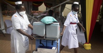 Health workers move vaccine cooler boxes to vaccination points at the official launch of Uganda's COVID-19 vaccination campaign at Mulago National Referral Hospital on March 10, 2021.