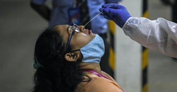 A health worker takes a nasal swab sample to test a woman for COVID-19 in Mumbai, India.