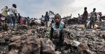 Children stand amidst lava from the volcanic eruption of Mount Nyiragongo, which occurred late on May 22, 2021 in eastern Democratic Republic of Congo.