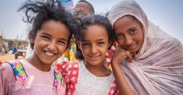 Three Malian girls pose outside the food distribution center at the UNICEF-supported Mbera refugee camp in Mauritania.