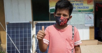 A boy in San Joaqín de Omaguas, Peru welcomes the arrival of one of 1,100 solar-powered freezers procured by UNICEF Supply Division for the safe storage of vaccines in Peru.