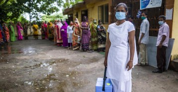 Nilam Bamaniya, a 23-year-old general nursing midwife, holds a vaccine carrier filled with vaccine doses for a COVID-19 vaccination session at a UNICEF-supported public health center in Samlaya, Vadodra, Gujarat, India on July 20. 2021.