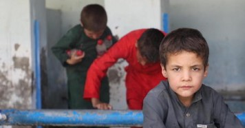 Children displaced by violence fill bottles with water near Peer Mohammad Kakar High School in Dasht-e-Padola, southern Kabul, Afghanistan on August 14, 2021.
