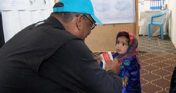UNICEF Representative in Afghanistan Hervé Ludovic de Lys greets a girl enjoying a packet of Ready-to-Use Therapeutic Food (RUTF) at a clinic in the Sabz-e-Shark camp for internally displaced persons in Herat on September 29, 2021.