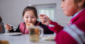 Nurel, 7, a primary school student, eats a healthy lunch prepared by a cook at Shabdan Baatyr school near Shabdan village, Chon Kemin valley, Kyrgyzstan.