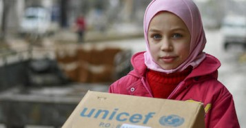 Najwa, 10, received a box of new winter clothes from UNICEF in Hammourieh, rural Damascus in the Syrian Arab Republic.