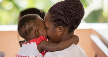 One-year-old Emily plays with her mother as they await immunization services at UNICEF-supported Kiswa Health Centre III in Uganda.