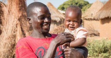 One-year-old Moses and his father, Ponsilio Phiri, play in Zambia in 2020. Baby Moses and his family are enrolled in the playful parenting program supported through UNICEF by the Lego Foundation.