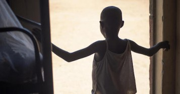 An 8-year-old girl — the youngest ever rescued by Kenyan and Ugandan police from female genital mutilation (FGM) — stands in a doorway at Kalas Girls Primary School in Uganda's Amudat District in 2020.