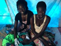 Florence (left) – a trained midwife – checks on the baby, and his mother Kuei, shortly after the baby's birth. © UNICEF South Sudan/2014/KentPage