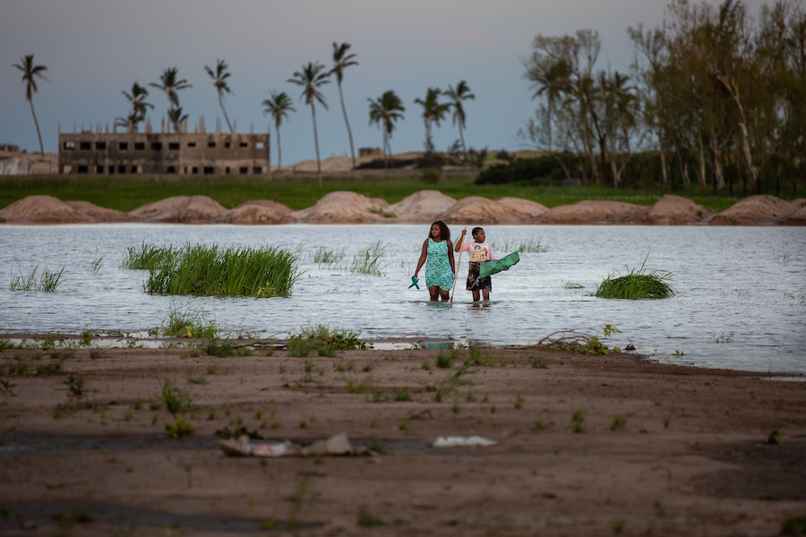 A woman and child walk through a flooded area of Sofala province outside the port city of Beira, Mozambique where Cyclone Eloise made landfall on Jan. 23, displacing thousands.