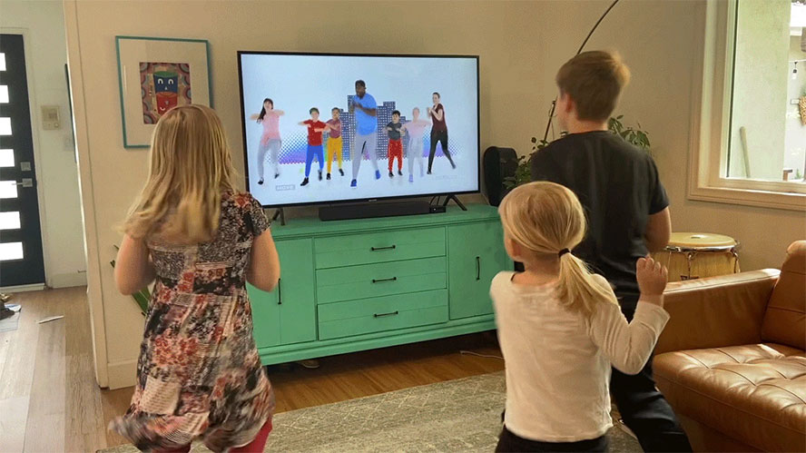 children exercise in their livingroom in front of a video of group exercise