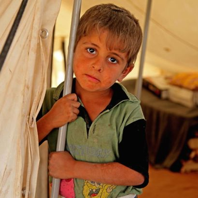 5-year-old Ali Saleh, whose family has been displaced from the Kokjeli area in the conflict-affected city of Mosul, stands by a pole at the entrance to a tent in the Khazar transit camp in the northern-eastern city of Erbil, capital of Kurdistan Region