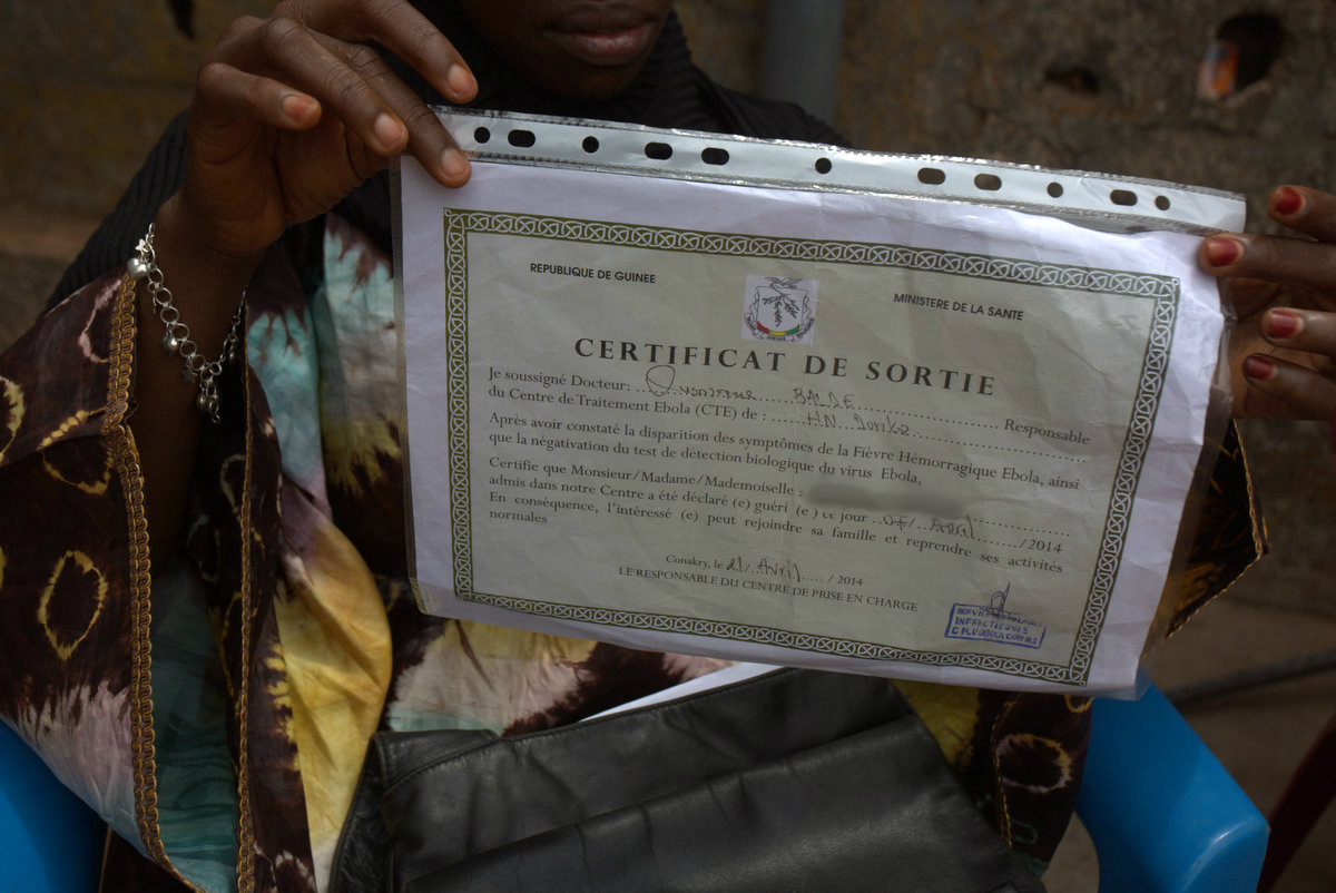 Kadiatou, an Ebola survivor in Guinea, holds up the certificate declaring her healthy status. (c) UNICEF Guinea/2014/Timothy La Rose