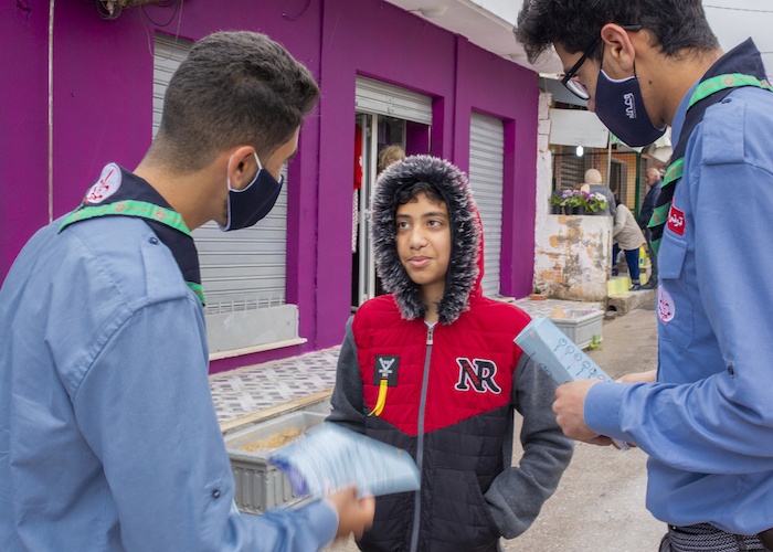 Two Scouts speak to a child in Mhamdia, a Tunis suburb, about the importance of wearing a mask to prevent the spread of COVID-19.