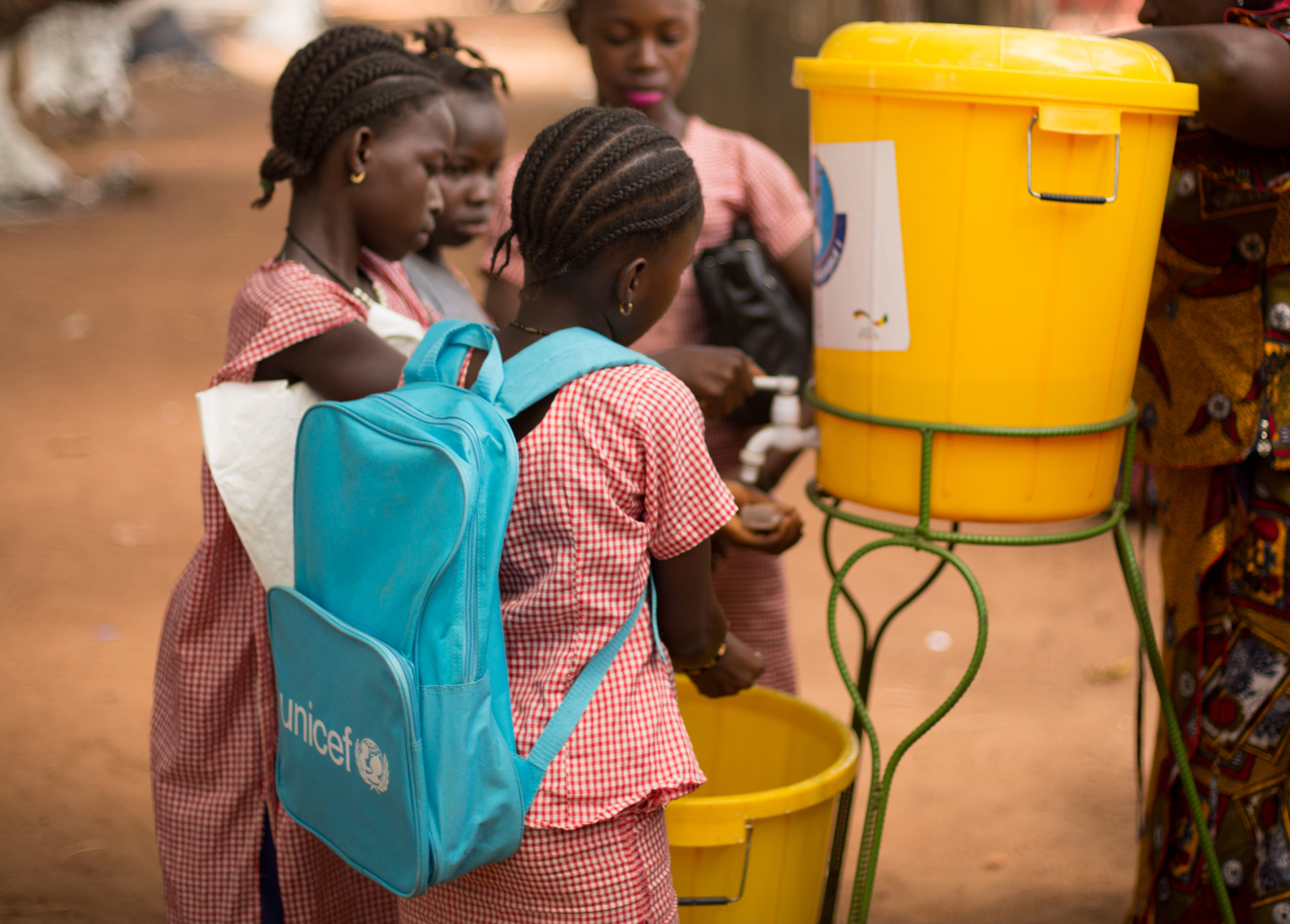 children in a UNICEF backpack getting water from a water cooler