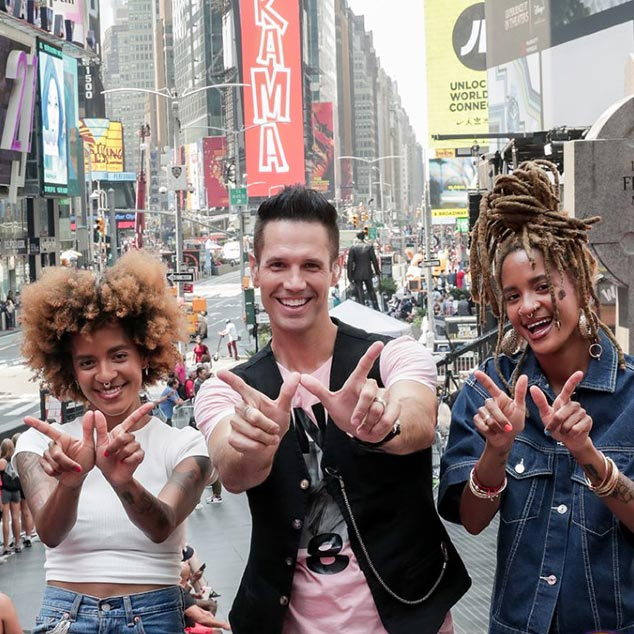 Three people in Times Square each make a W symbol with their hands