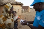 A UNICEF worker brings Rougui Sal a supply of fortified peanut paste for her two-year-old son, Idy. © UNICEF/Mauritania/2012/Mia Brandt