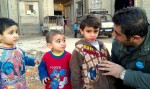 A UNICEF staff member talks with children at a displaced persons shelter in Homs. ©UNICEF/Syria 2012