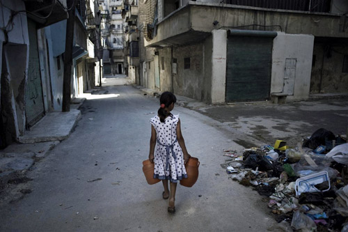 A girl carries jerrycans of water in Aleppo, Syria.