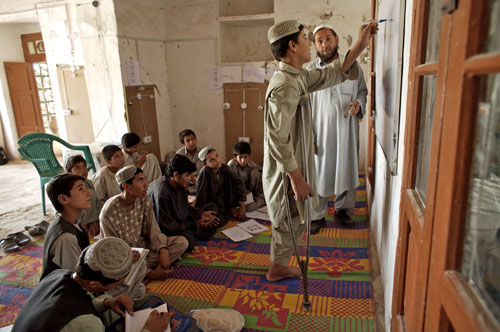 Rahmatuallah, 14, writes on a white board during a workshop for electricians at a UNICEF-assisted reintegration and rehabilitation center in Kandahar.
