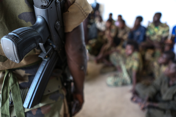 An armed soldier looks on near a group of 21 children, aged 14-17, who were released from armed groups following a series of meetings between UNICEF and the President of Central African Republic Michel Djotodia. © UNICEF/NYHQ2013-0242/JORDI MATAS